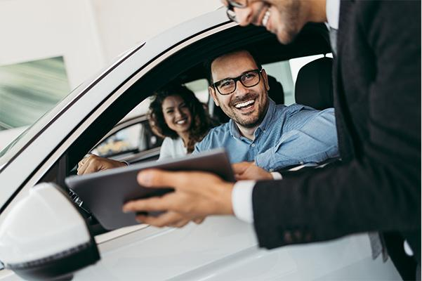 Car Salesman helping a happy couple find their perfect car