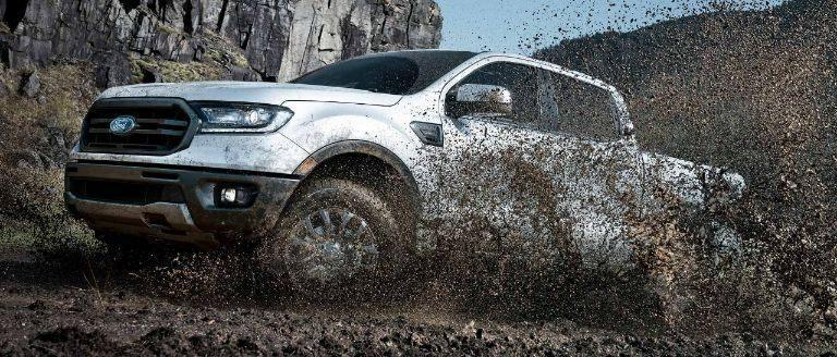 White platinum Ford Ranger crashing through mud while offroading