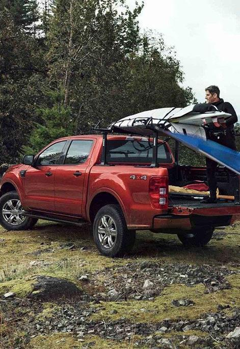 Unloading a surf board from a Hot pepper red Ford Ranger parked near trees