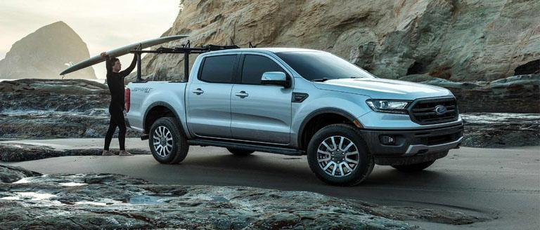 Loading a surfboard onto an Ingot silver Ford Ranger Sport parked on sand