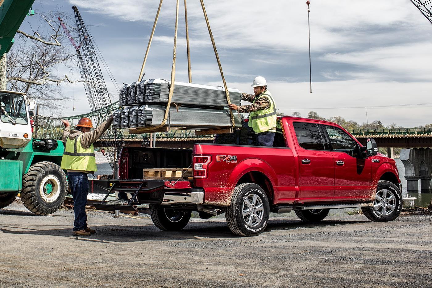 Loading red Ford F-150 Supercrew with metal from a crane