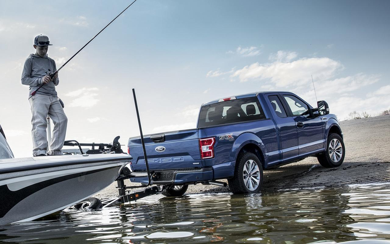 Blue Ford F-150 towing a boat in water