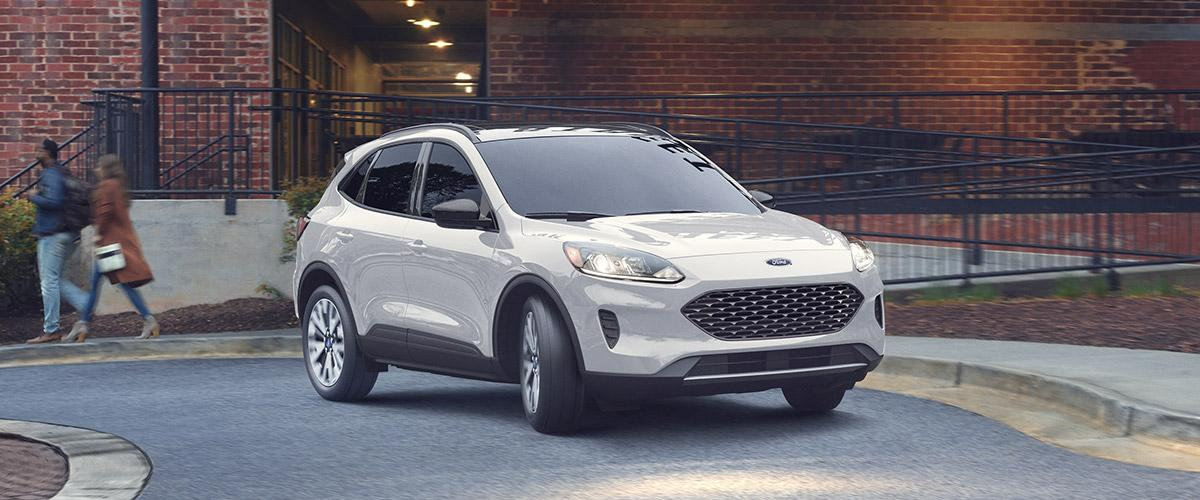 frontal view of white Ford Escape crossover parked in front of a red brick building