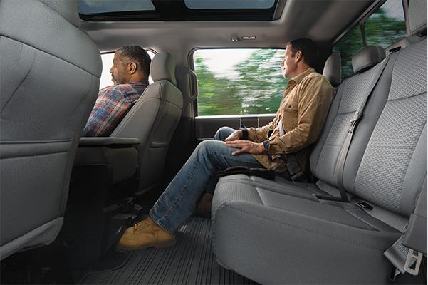 interior rear view of the Ford F-150 pickup truck with one person sitting in the back seat showcasing the large legroom