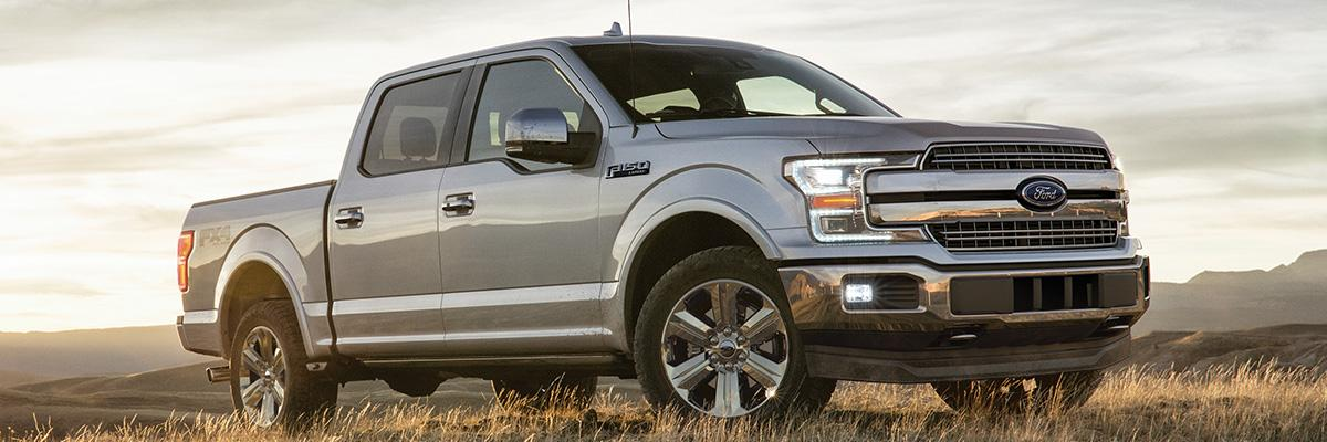side view of silver Ford F-150 pickup truck parked on top of a mountain