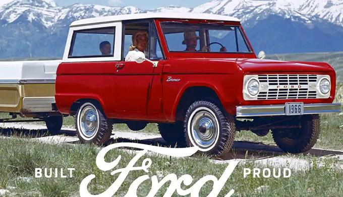 A family riding in a 1966 Ford Bronco Sport Wagon in Royal Maroon with Wimbledon White roof pulling a pop up camper trailer on a two track trail in the mountains