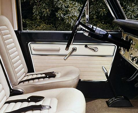 A 1967 Ford Bronco Sport interior with Parchment Vinyl driver and passenger bucket seats.