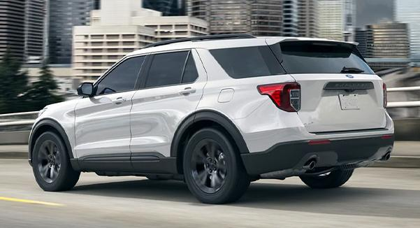A 2021 Ford Explorer being driven down the highway with a cityscape in the background