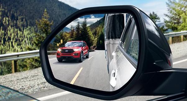 Close up of an auto dimming sideview mirror showing the reflection of a 2021 Ford Explorer in Lucid Red
